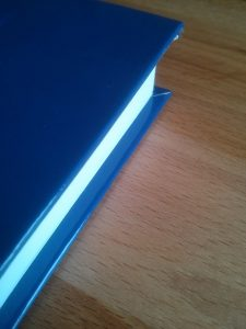 """The """"hang over"""" of the cover over the book block."""