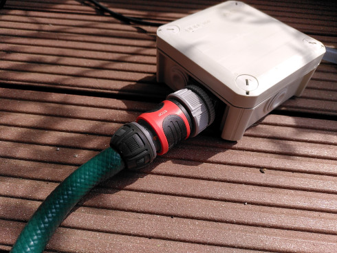 """A 3/4"""" hose connected to the water solenoid valve enclosure"""